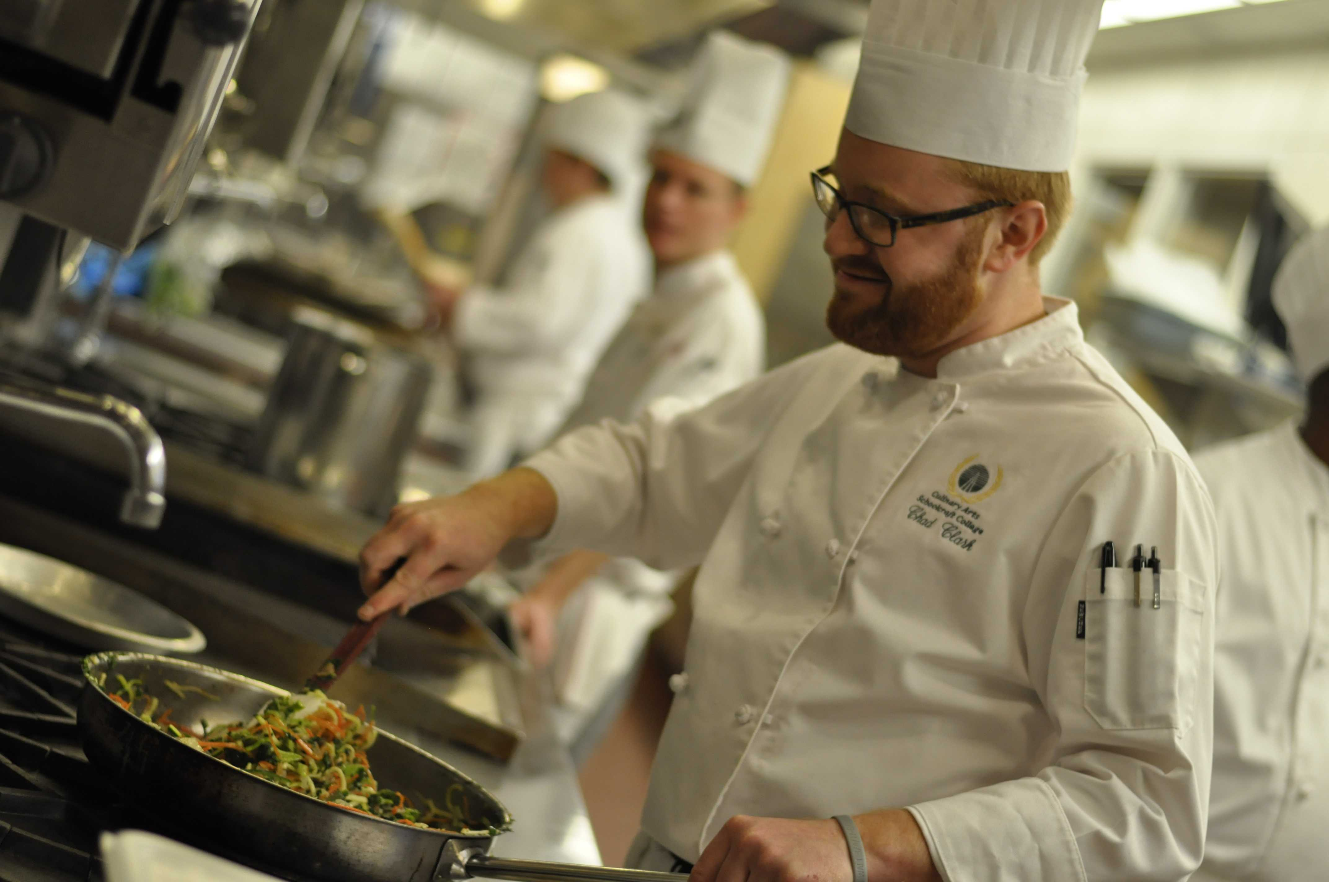 Chad Clark works on part of the ingredients needed to make vegetable lasagna. Photo by Nathan Gartner.