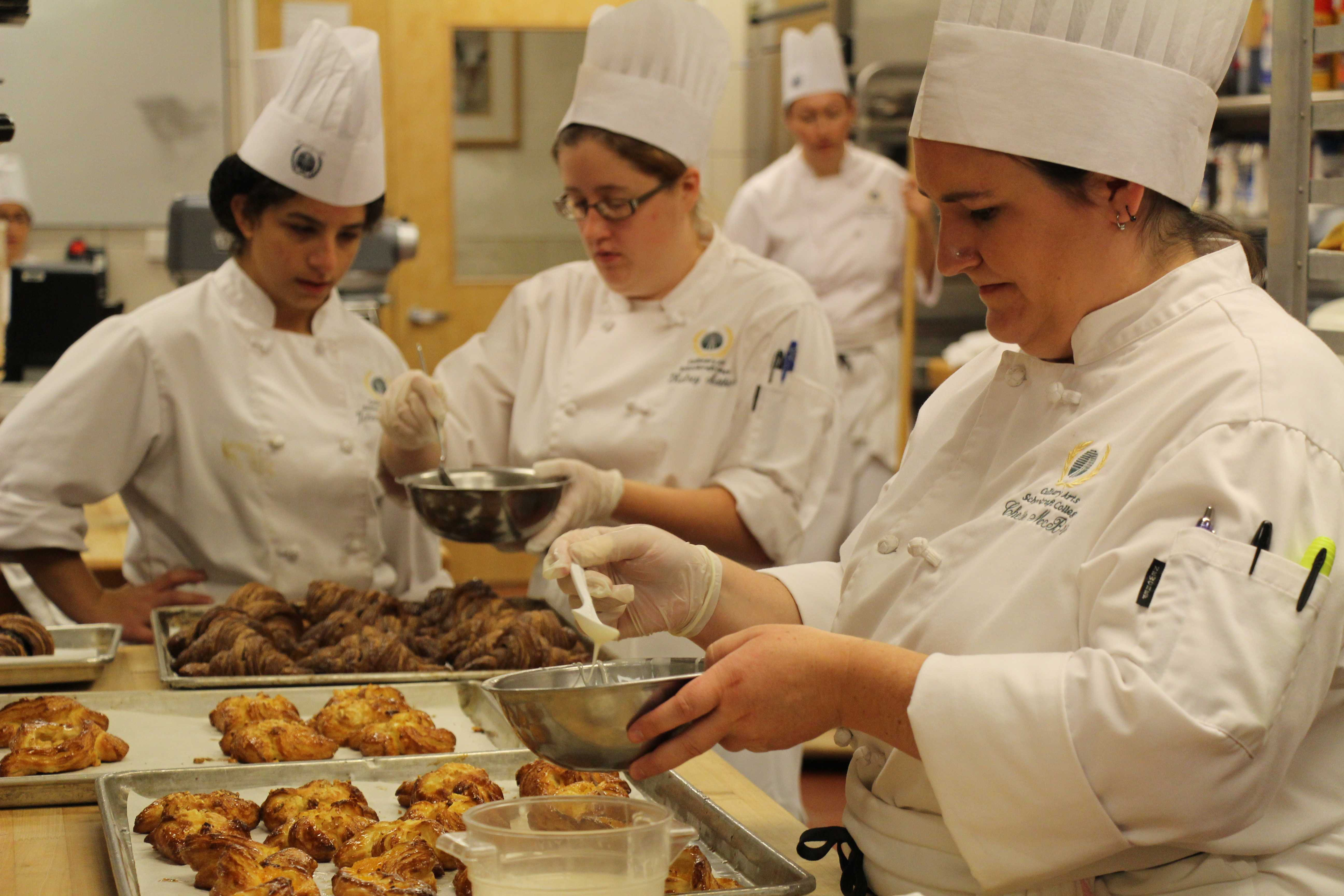 (From left to right) Julianna Nicholas, Kelsey Mathias, and Cherie McBride put the finishing touches on pastries that will be served at the American Harvest Resturant in the VistaTech Building later in the day. Photo by Nathan Gartner.