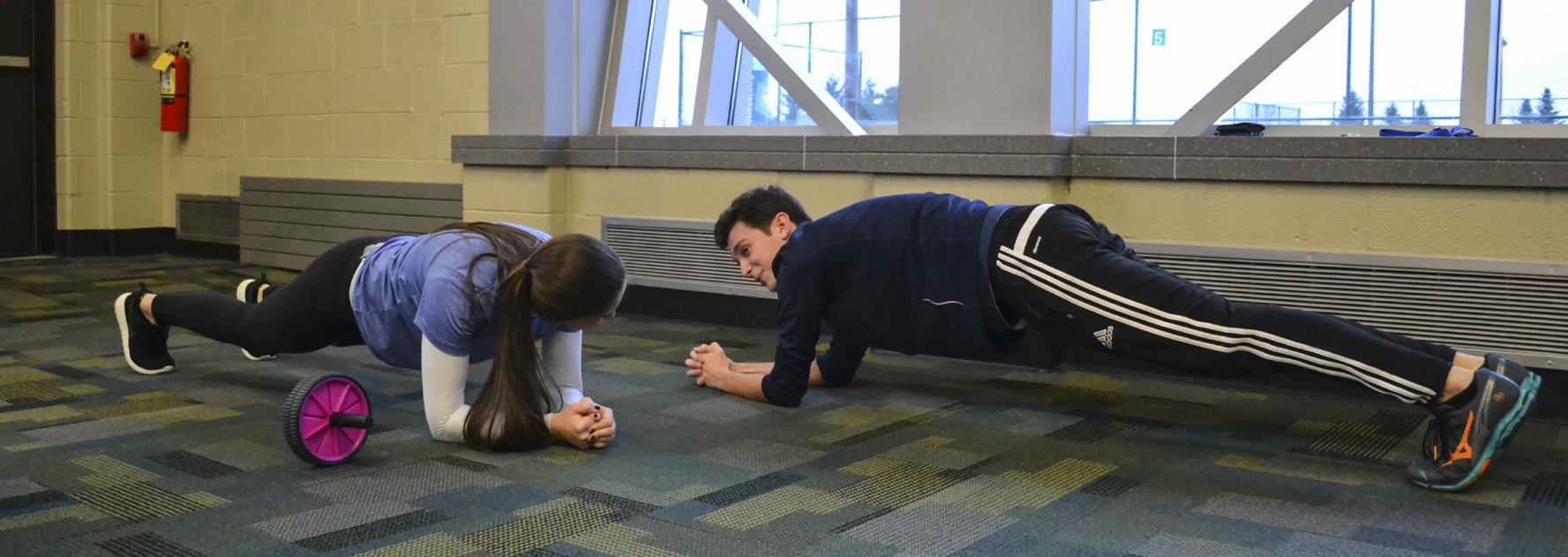 Club leaders Maggie Leins and Frank Suchy work on their core stability by doing planks. PHOTO BY MIRANDA MALEC|STAFF PHOTOGRAPHER