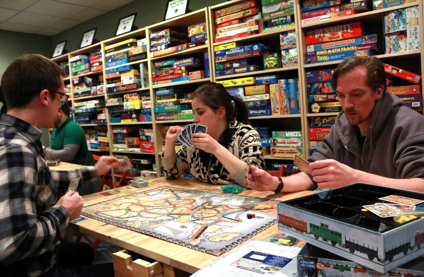 PHOTO BY ANDREW RELLINGER|STAFF PHOTOGRAPHER 3&UP Board Game Lounge in Downtown Plymouth is a safe haven for some good-old-fashioned board game fun. (from left to right) Joe Gudobba of Dearborn, Becky Rea of Northville and Jon Stoddart of Garden City enjoy a collection of over 1,000 games from the 1950s through today at the new lounge.