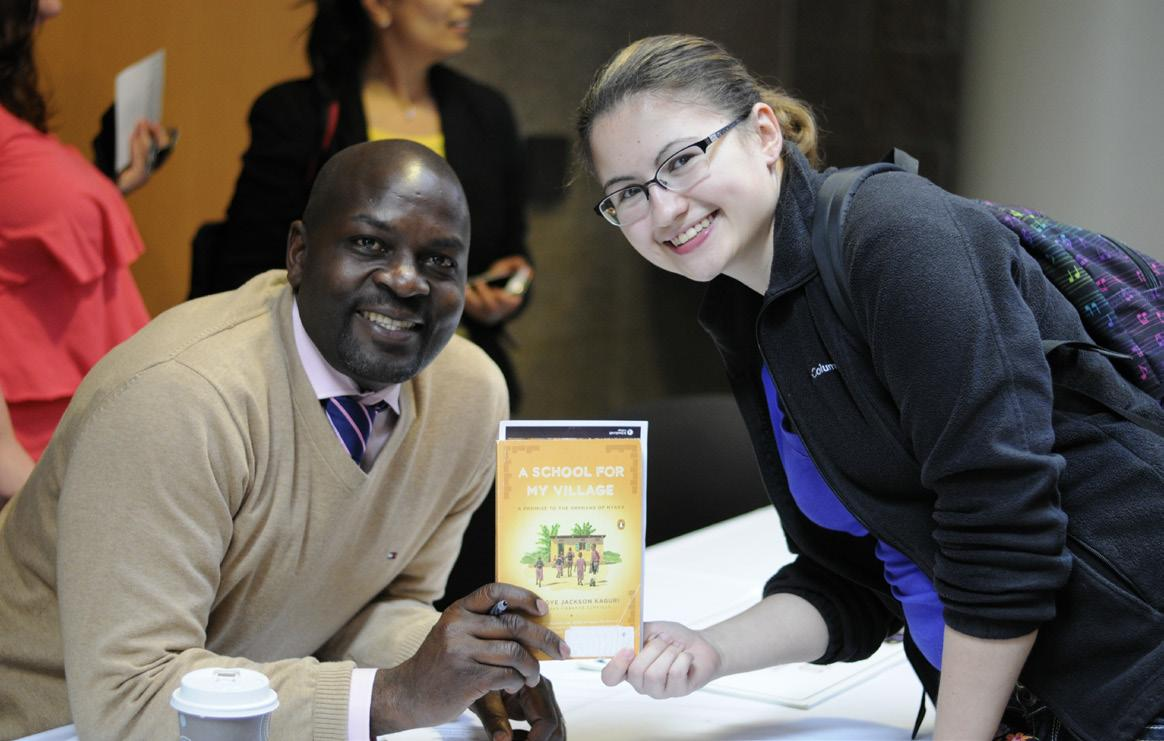 "PHOTO BY NATHAN GARTNER PHOTO EDITOR Kaguri, left, poses with Raya Lasiewski, holding a copy of his book ""The Price of Stones: A School for My Village."""