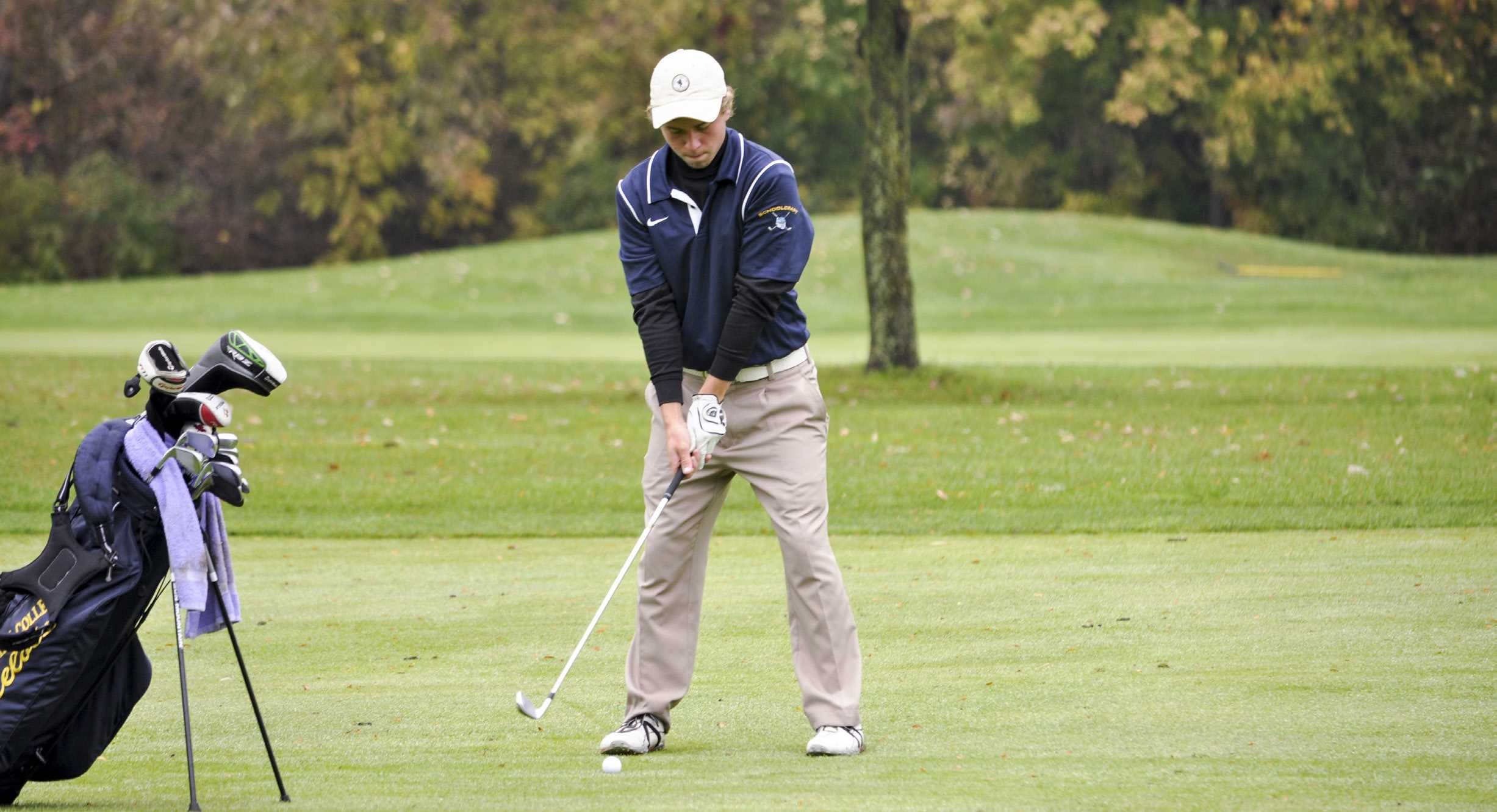 Sophomore Austin Harris eyes up his approach shot as he tries to hit the ball near the hole in the Schoolcraft College Invitational.