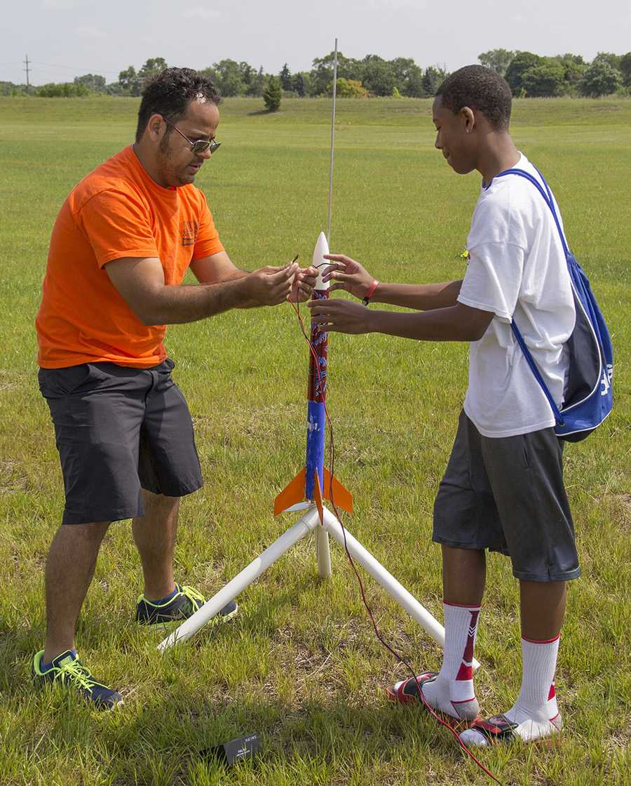PHOTOS BY ELLEN J. HOCHBERG Rocket Science instructor Jordan Orlewicz, left, assists a student with his rocket prior to the launching.