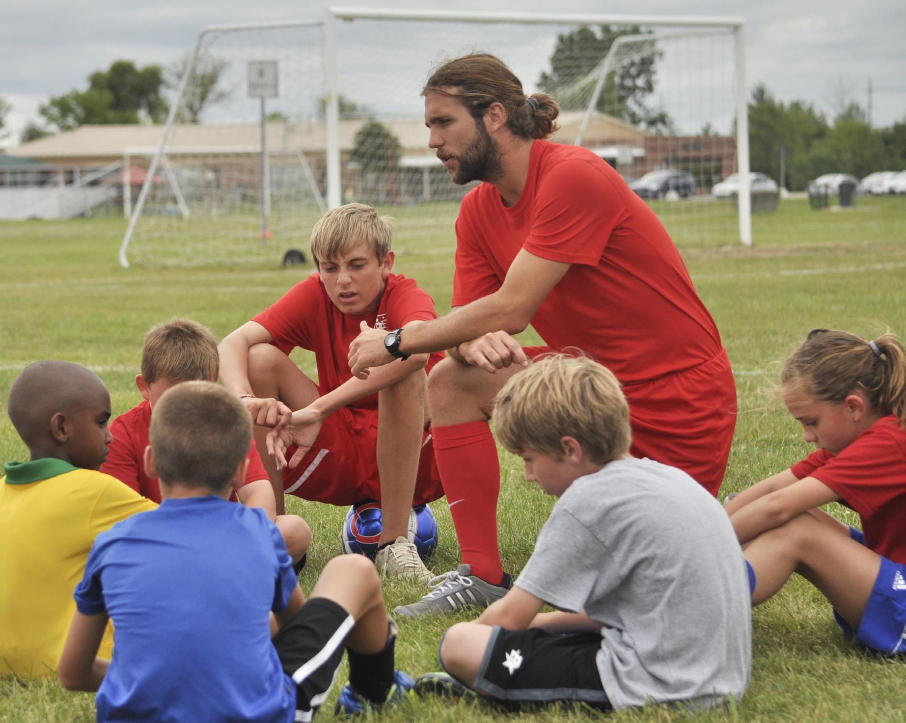 PHOTOS BY NATHAN GARTNER PHOTO EDITOR Schoolcraft Athletic Support Services Coordinator Ryan Lemasters instructs campers on fundementals before they partake in some drills during a Victory Soccer camp in August 2014.