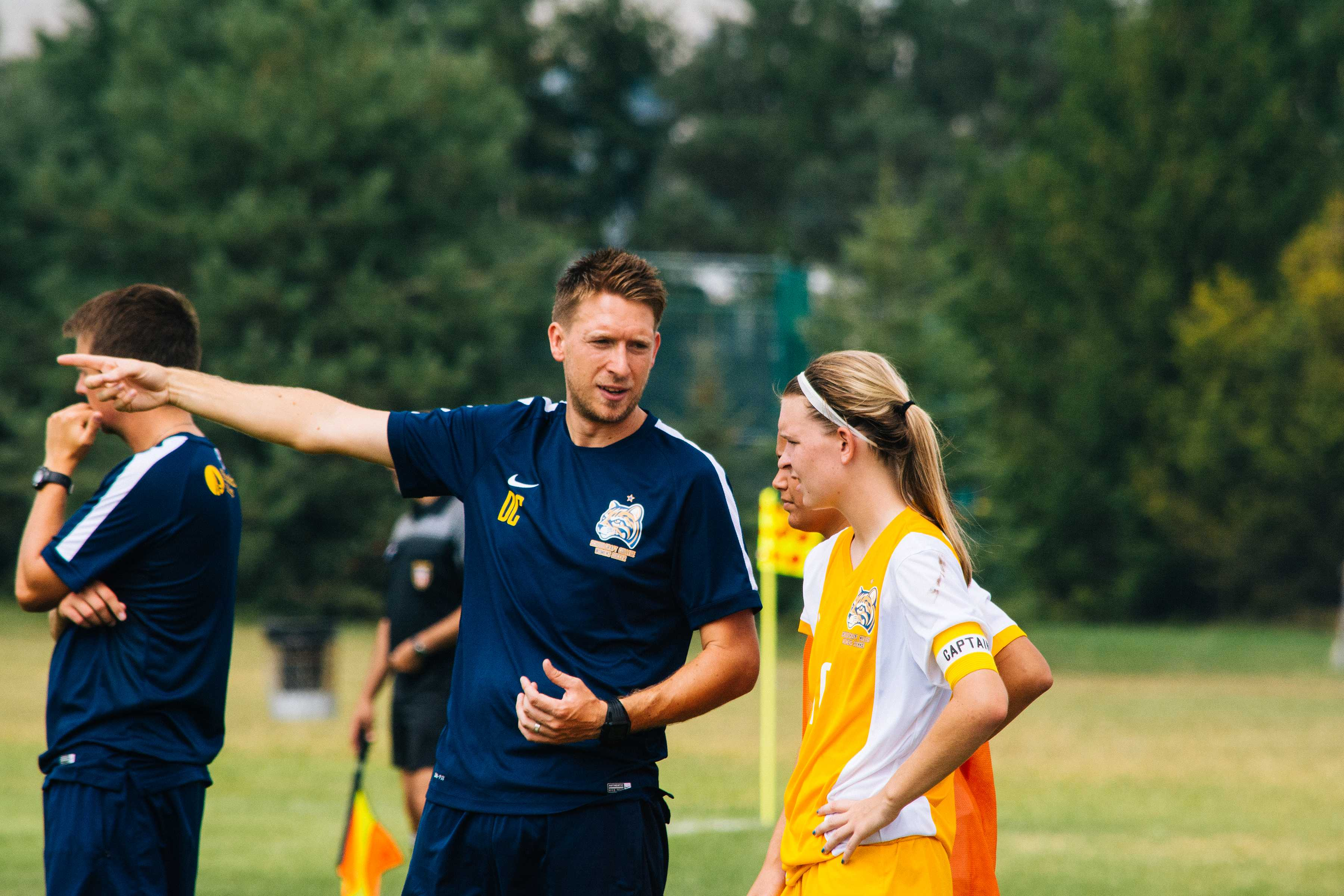 Head Coach of the Schoolcraft College Women Soccer team, Dave Carver, discusses strategy with one of the Lady Ocelots during their game Sunday afternoon.