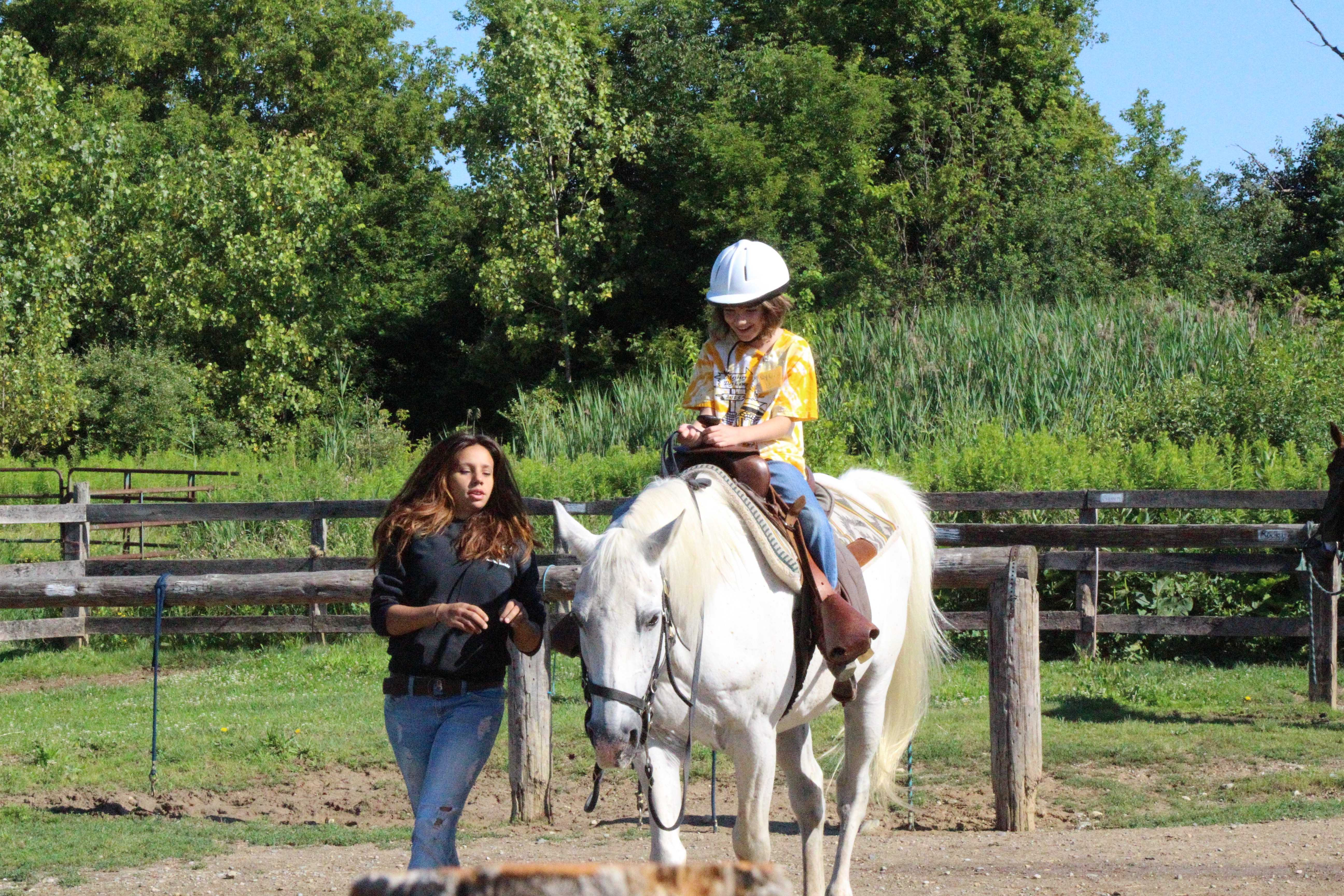 A staff member helps guide a horse and excited rider to the waterhole before the day's ride.