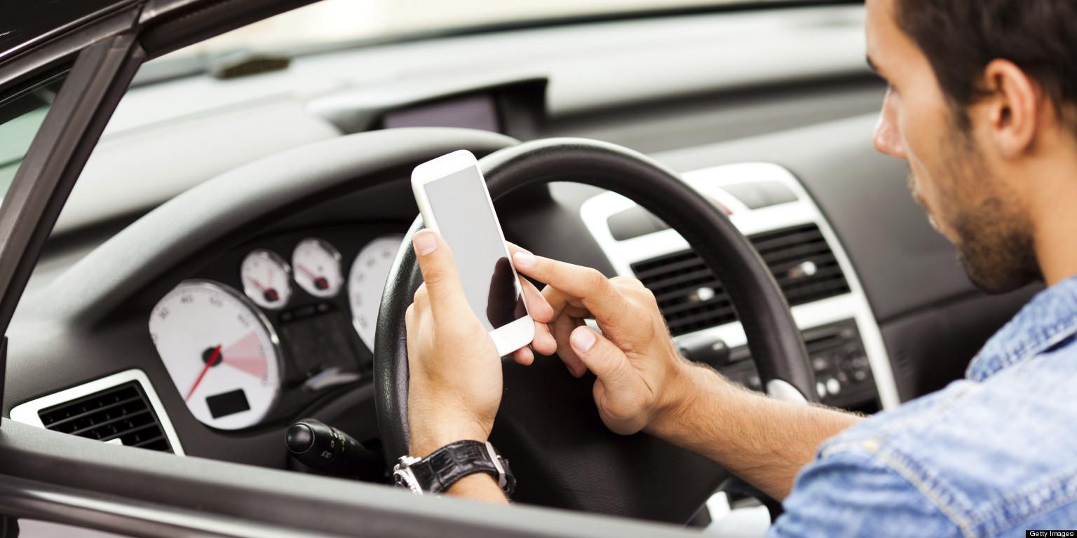 Young man using smart phone in his car