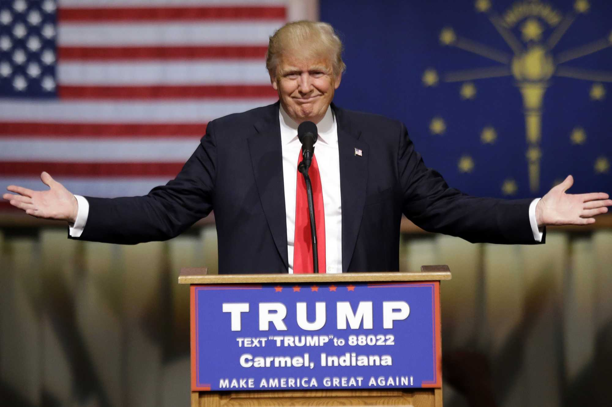 Donald Trump at a podium with spread hands.