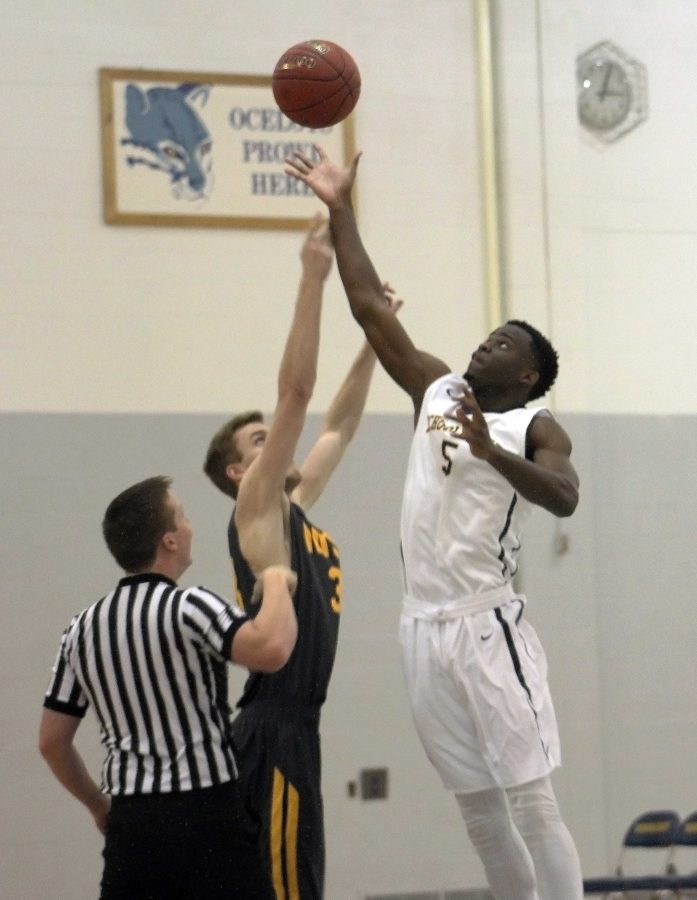 Schoolcraft%E2%80%99s+Tariq+Jones+goes+in+for+a+tip+off+against+Mott+Community+College+player%2C+Sean+Corcoran.