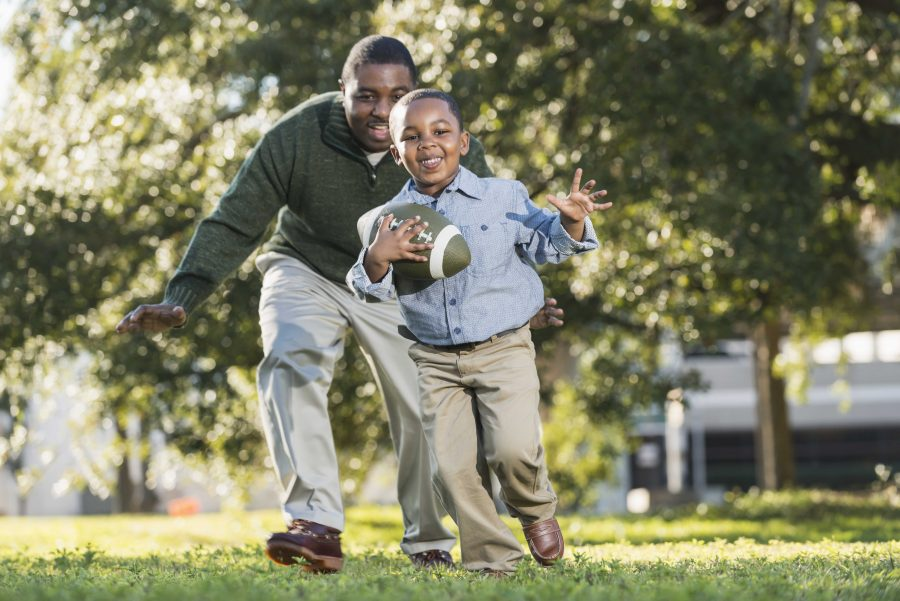 An African American man in his 40s playing football with his 5 year old son. It is a bright, sunny spring day. They are outdoors in the park or the yard, trees out of focus in the background. The boy is holding the ball, running, and his dad is chasing him from behind.