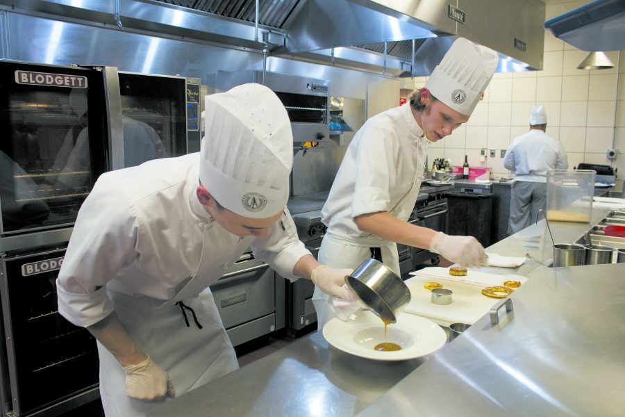 Students Jeff Schuarce and Gavin Fritz (left to right) show close attention to detail as they prepare one of the dishes offered for dinner at the American Harvest Restaurant. The Harvest provides students with real world experience needed to work in the highly competitve culinary industry. (Photo by Chrissy Begle, Layout And Design Editor)