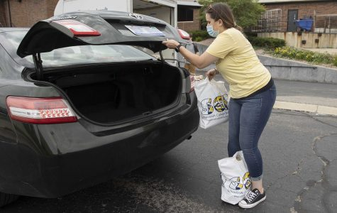 Megan Monthei, Membership Services Specialist at the Fitness Center places bags of non-perishable food into the trunk of the car of a Student Food Pantry recipient on June 26, 2020.