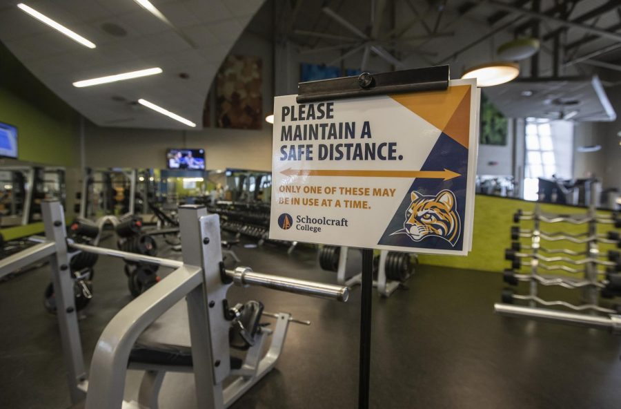 Signs reminding members to maintain a safe distance from one another are posted around the Fitness Center.