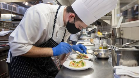 Austin Hannah puts the finishing touches on his seafood appetizer that consisted of: butter-poached lobster; butter-poached scallops; green leek puree as a base; pickled leeks; ricotta; and pancetta (a sort of cured bacon) during a practice session inside the Schoolcraft Culinary Arts kitchen.